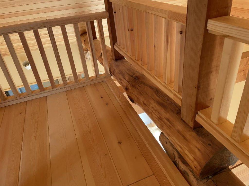 リビング上部に掛かる丸太の梁。 ロフトスペースを造り手すりを設置して、リビングダイニングと一体化