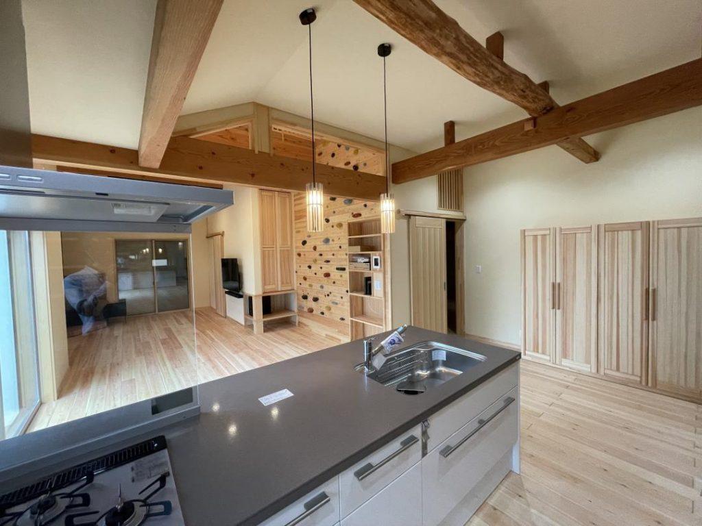 フラット対面からリビングダイニング 丸太の梁が癒してくれるキッチンのオープンな空間